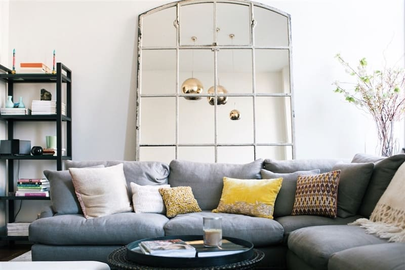 Neutral palette living room with large mirror and yellow accents.