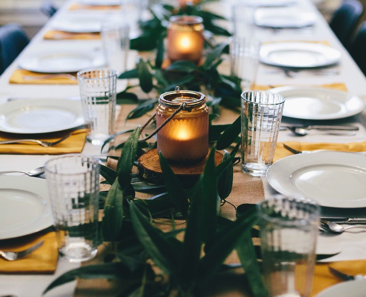 Tablescape with large leaves and candles.