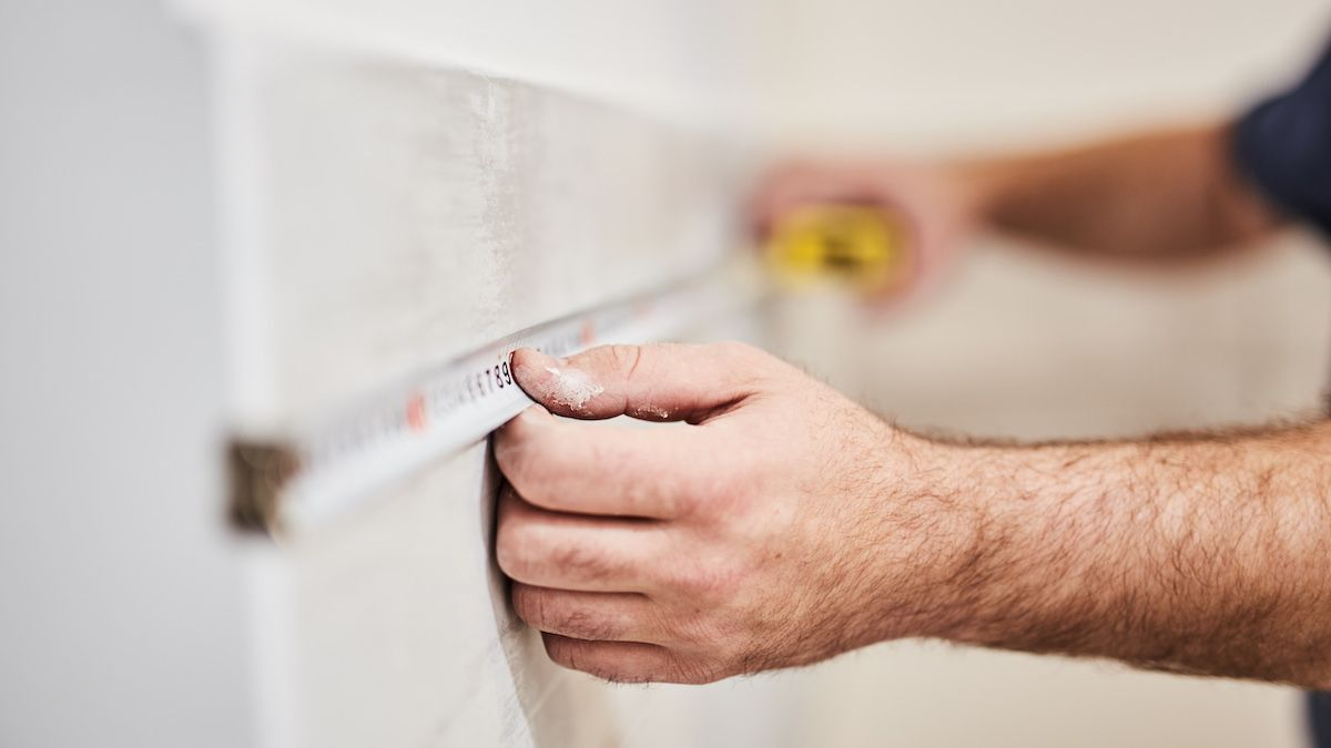 Man measuring wall with tape measure.