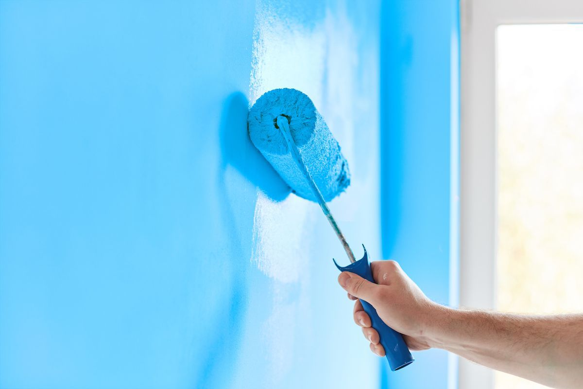 Man painting wall with roller.