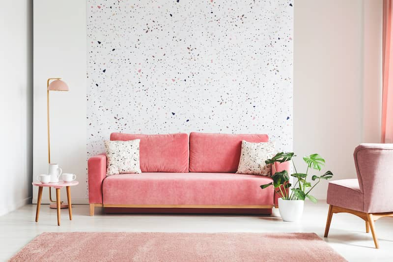 pink, velvet sofa, in front of lastrico wall in a living room interior