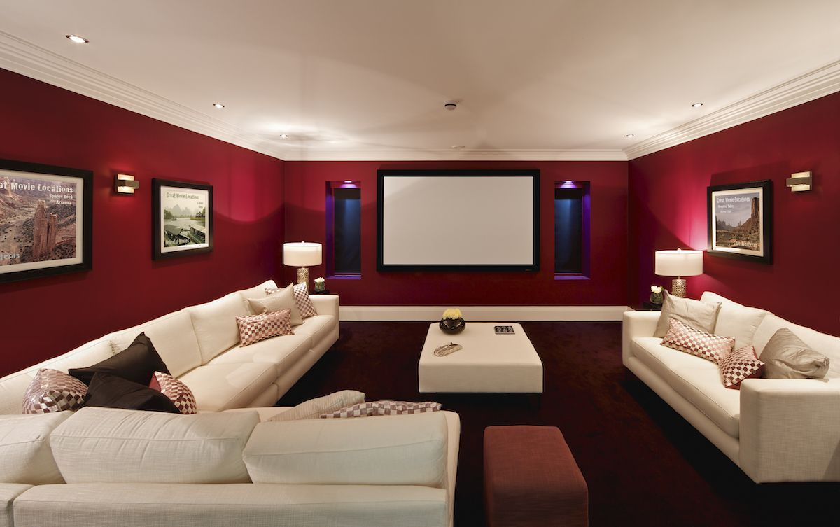 Basement outfitted with large screen and couches for a movie room.