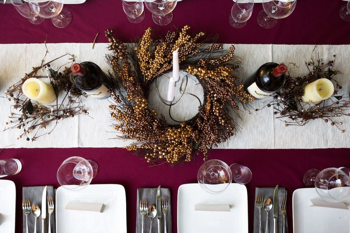 Neutral table runner over a berry-colored table cloth.