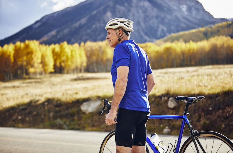Older man standing by a mountain bike with a mountain behind him