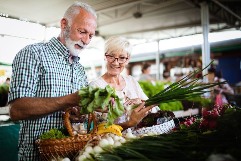 Senior couple picking out vegetables in a farmer's market in Iowa