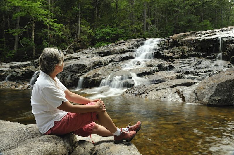 Senior woman relaxing by a waterfall in New Hampshire