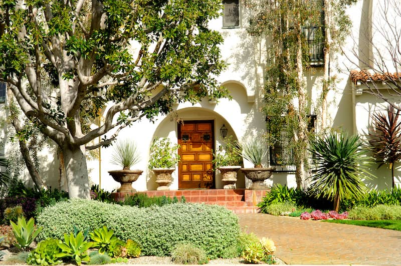 Spanish style front door surrounded by trees