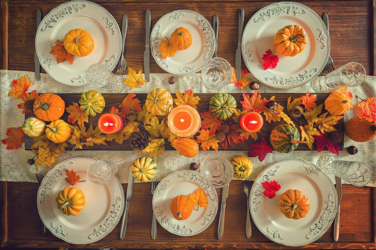 Thanksgiving table with mini pumpkins and gourds.