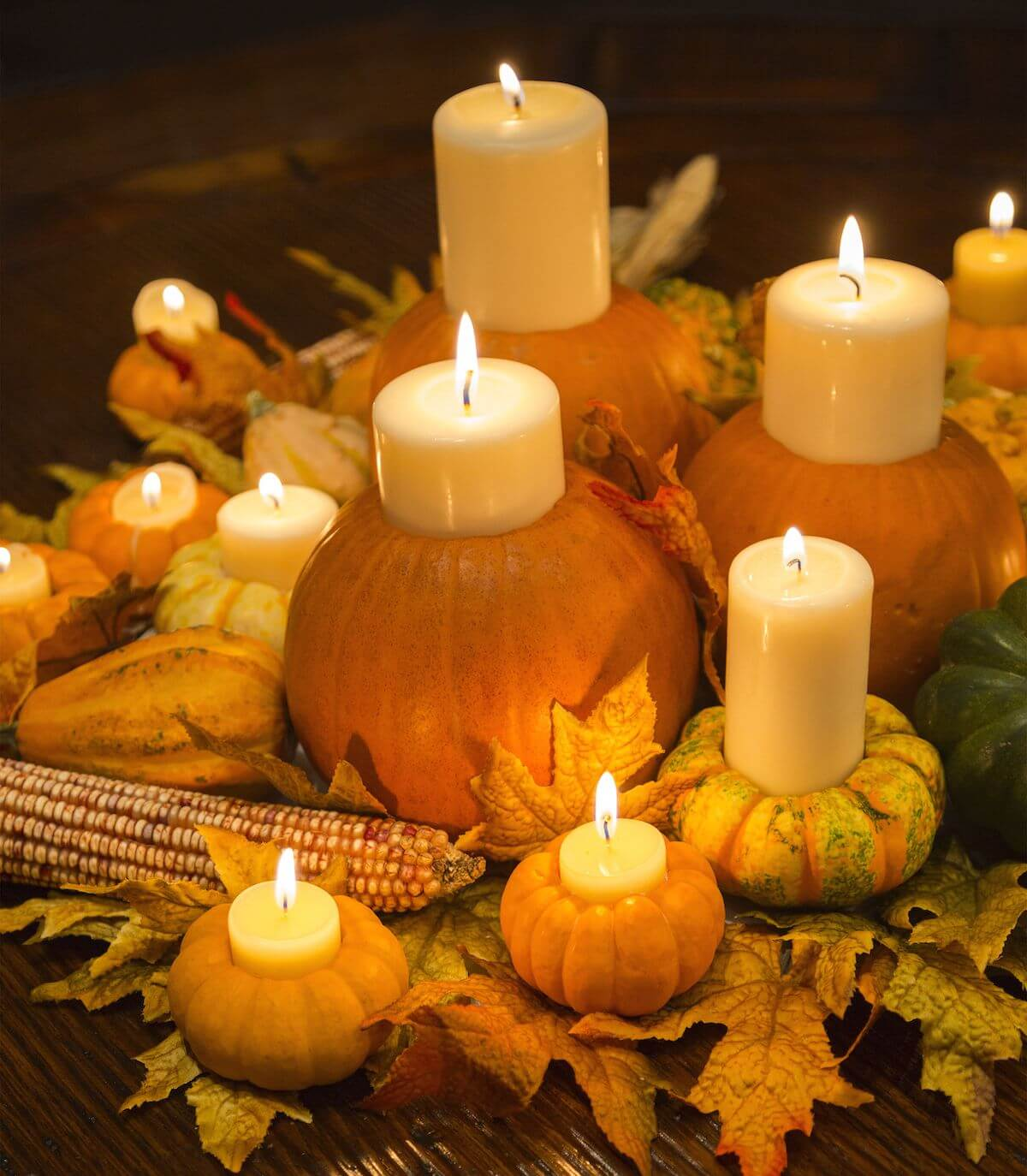 Pumpkins filled with candles on a bed of leaves.