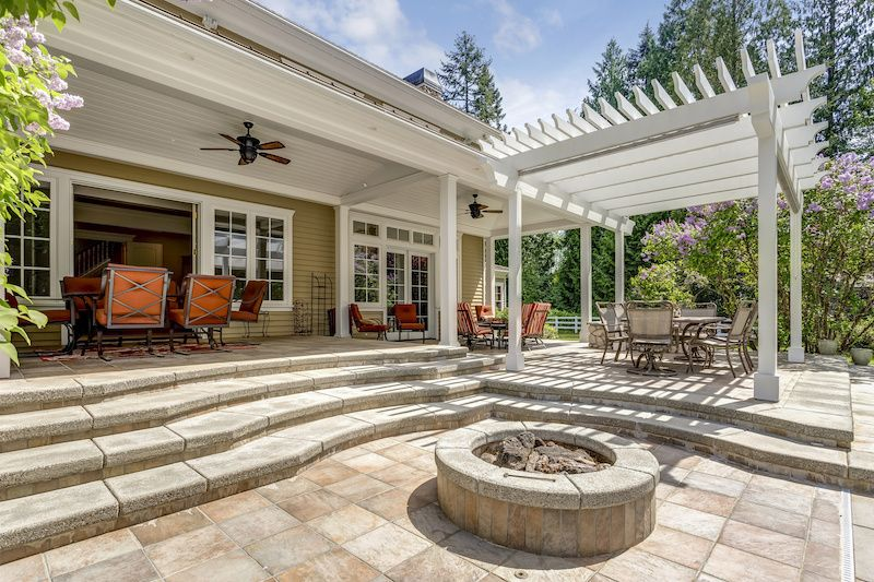 back yard with stone patio, fire pit and white vinyl pergola