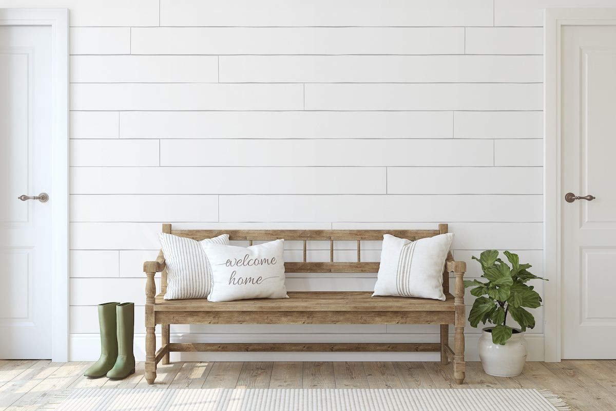 Welcome home pillow on an entryway bench in front of a shiplap wall.