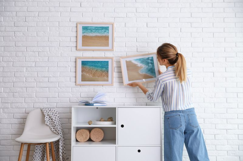 Woman hanging framed photos of the beach