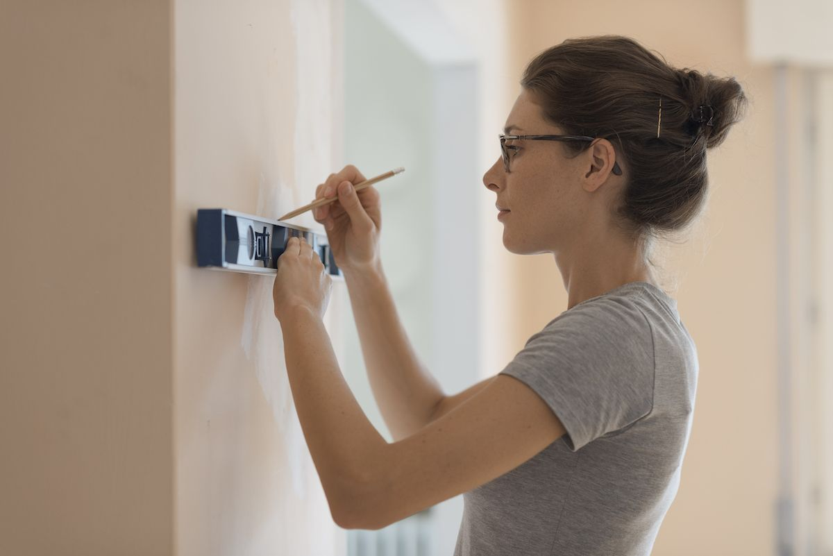 Woman using a level to measure on a wall.