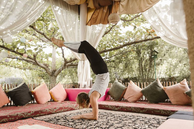 woman doing yoga underneath large pergola