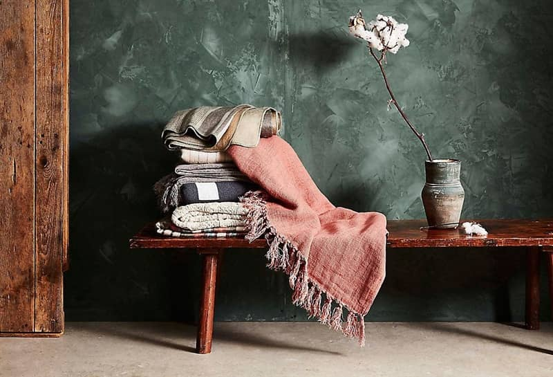 Stack of throw blankets on a wooden bench next to a vase with a single flower in it.
