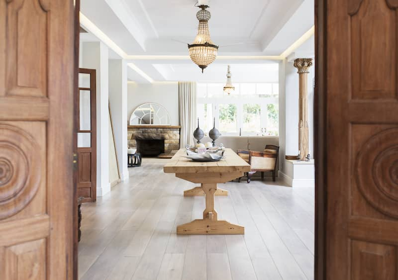 view between two woods doors showing a room with tray ceilings and a chandelier hanging from inside tray ceiling