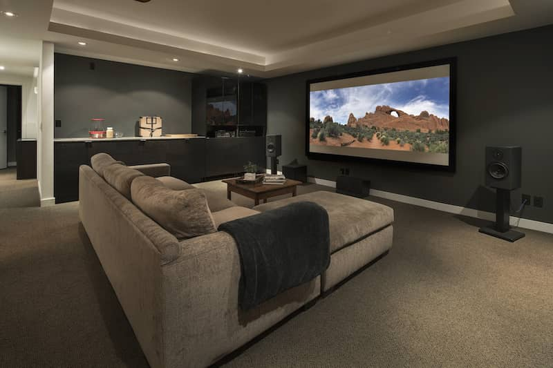 tray ceiling in a movie room in a home with a tray ceiling with lighting strip inside the edge of it