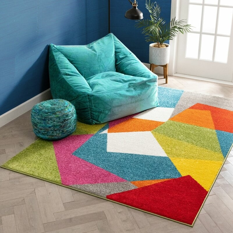 Vibrant living room with a teal beanbag chair and a colorful geometric design rug