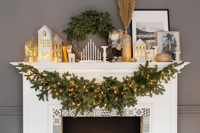 fireplace with christmas decor and greenery strung onit