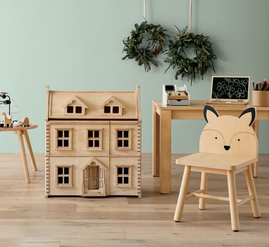A set of wooden kids furniture, with a chair, playhouse, desk, and make-believe cash register.