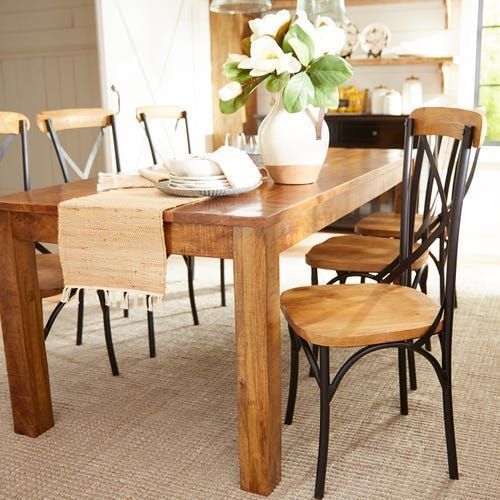Wooden table with wood and metal chairs surrounding it.