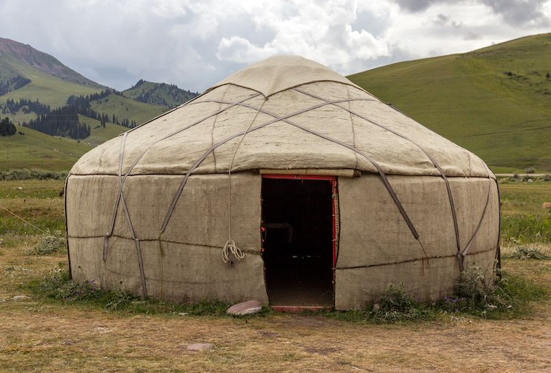 traditional yurt in a field near mountains