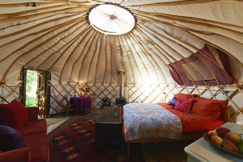 interior of a yurt with a bed and a dresser