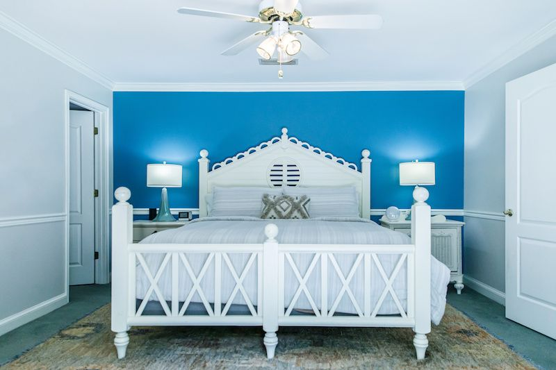 Bright blue accent wall in bedroom.