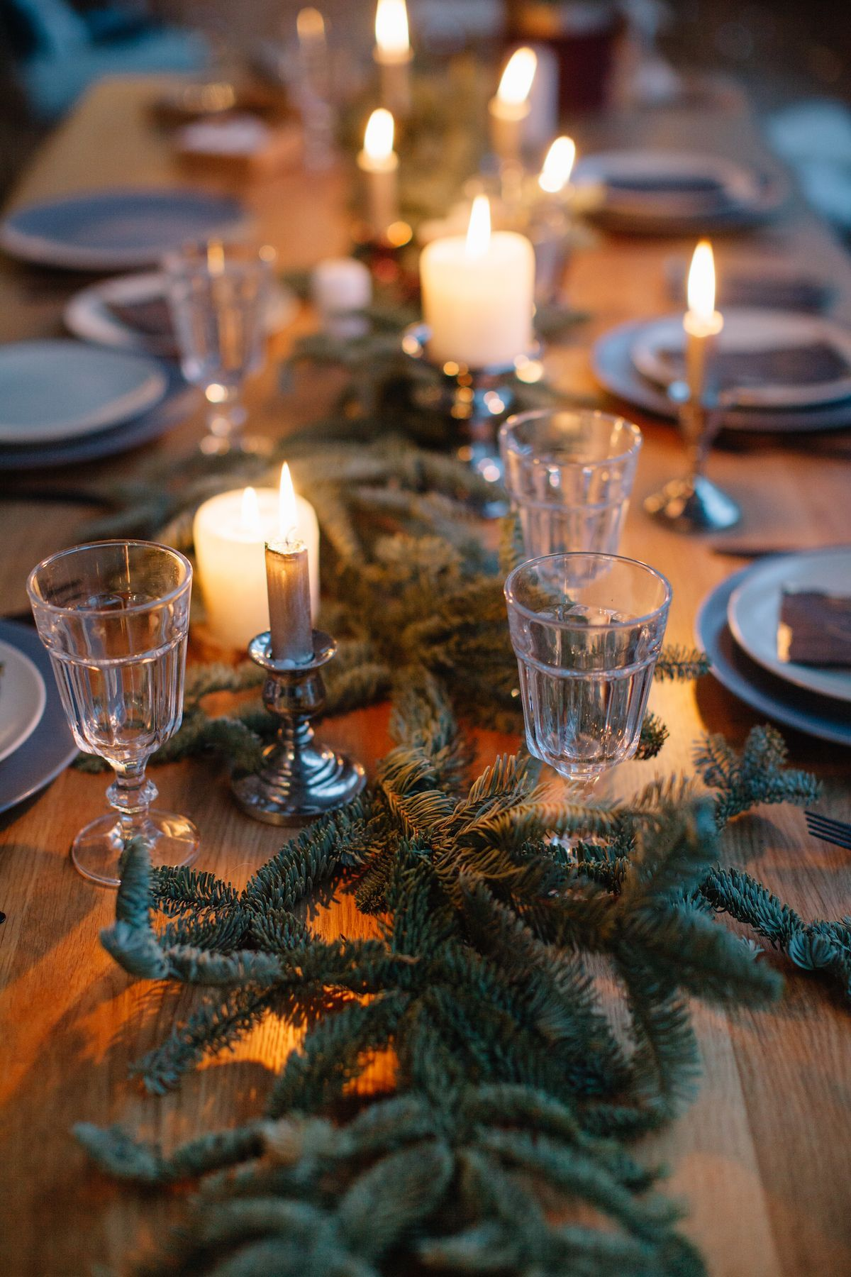 Elegant table with small candle sticks and traditional glassware.