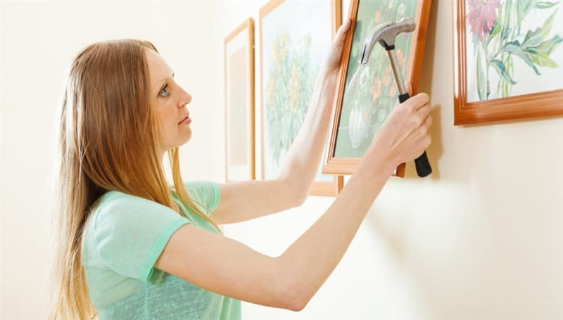 Woman hangs pictures