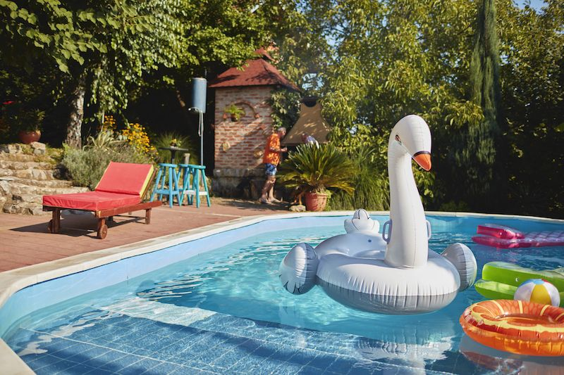 swan pool float surrounded by other floaties in in-ground pool