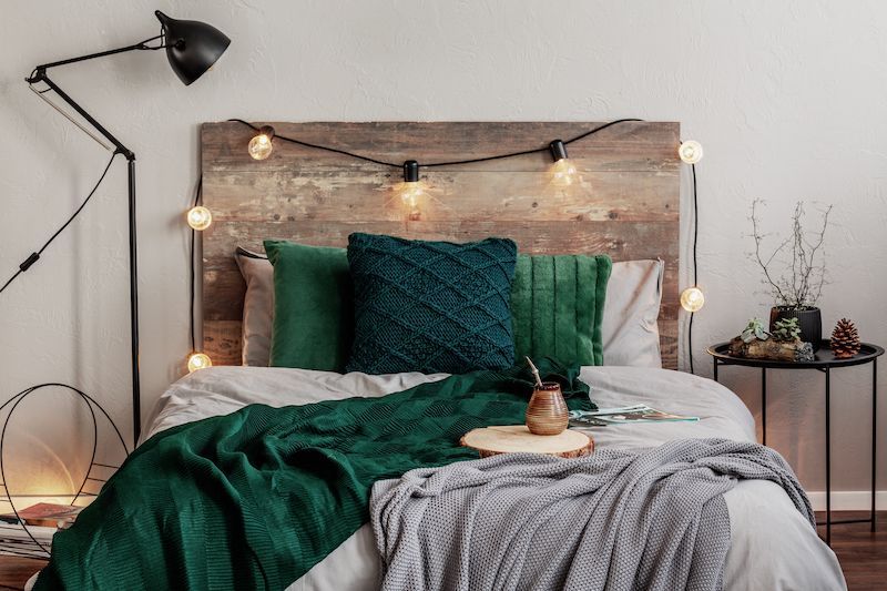 Rustic Wood headboard and bed with green decor.