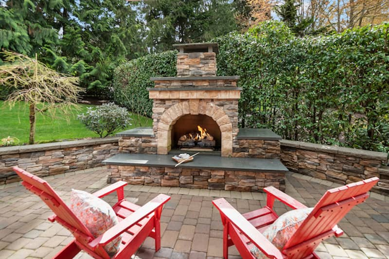 back patio with two red lawn chairs an outdoor brick fireplace